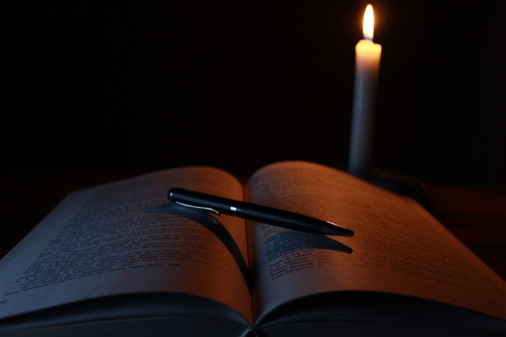 open book with a pen laying on it and a candle behond for the Wiccan rede