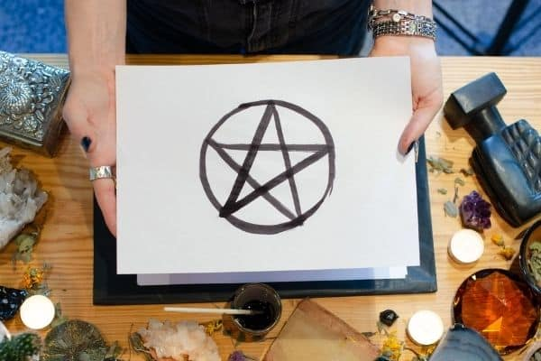 handdrawn pentacle being held in hands surrounded by candles