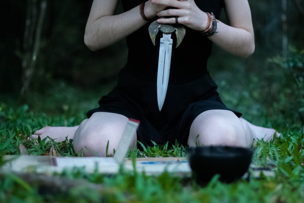 Woman using an Athame knife during a Wiccan ritual
