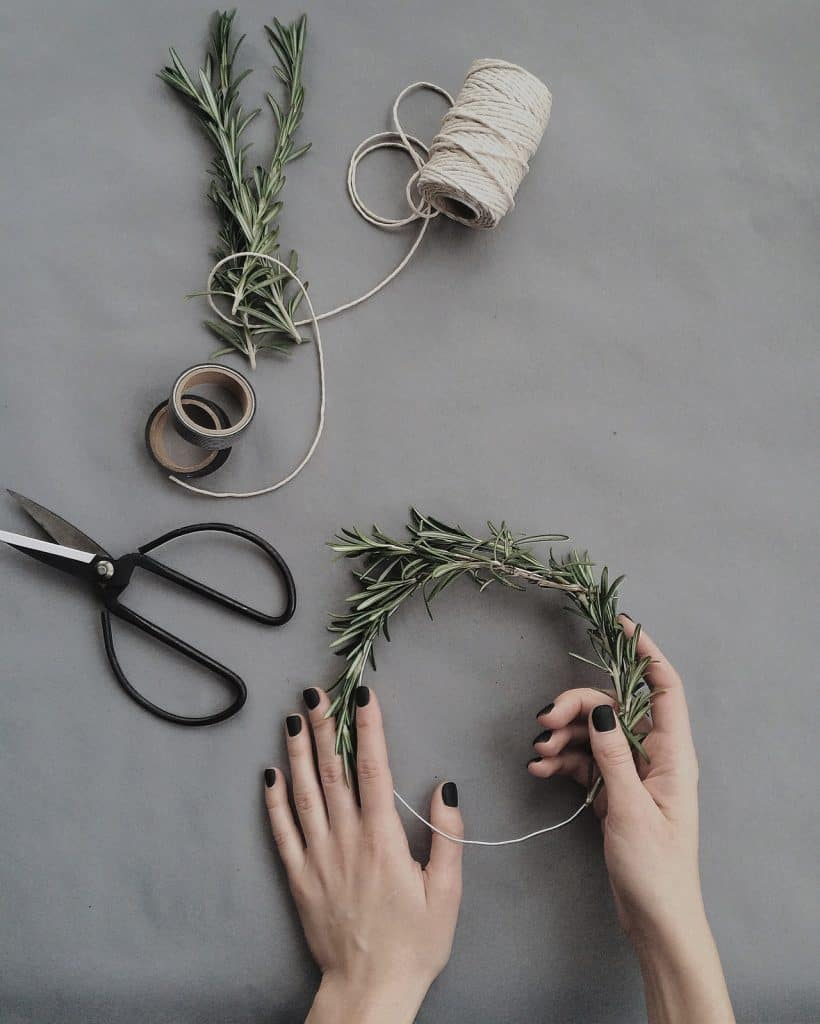 rosemary crown being made for a wedding with half made wreath, hands, scissors, rosemary and twine