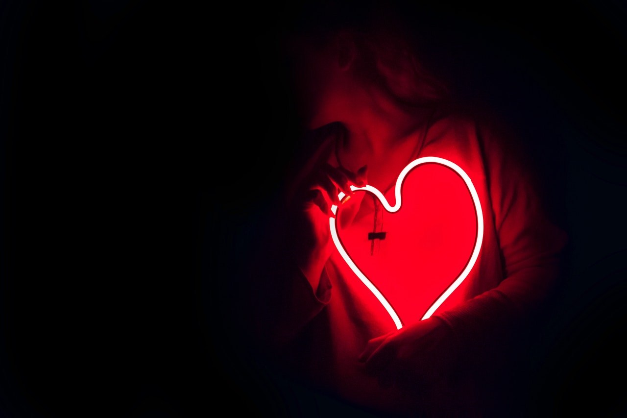 neon heart being held by person