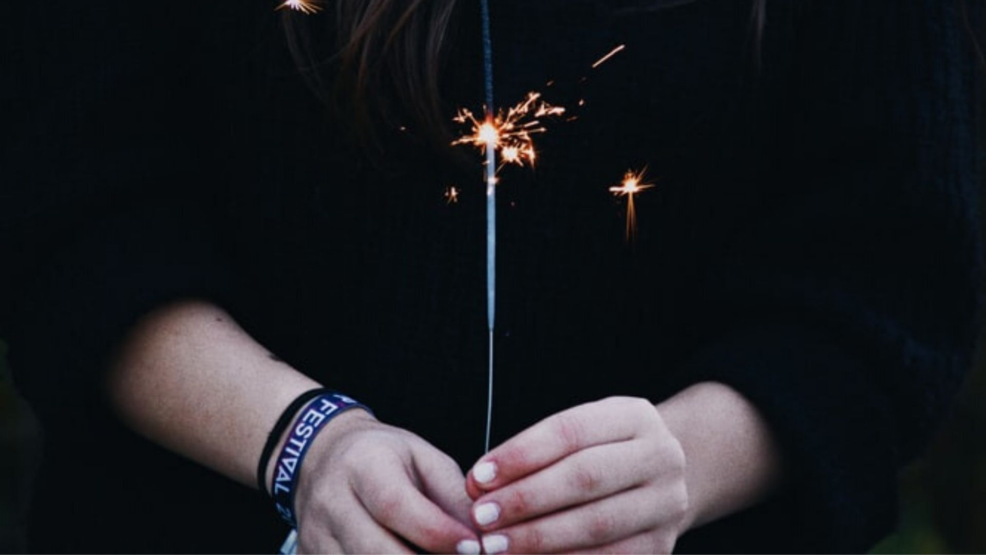 Imbolc ritual feature image of woman holding sparkler