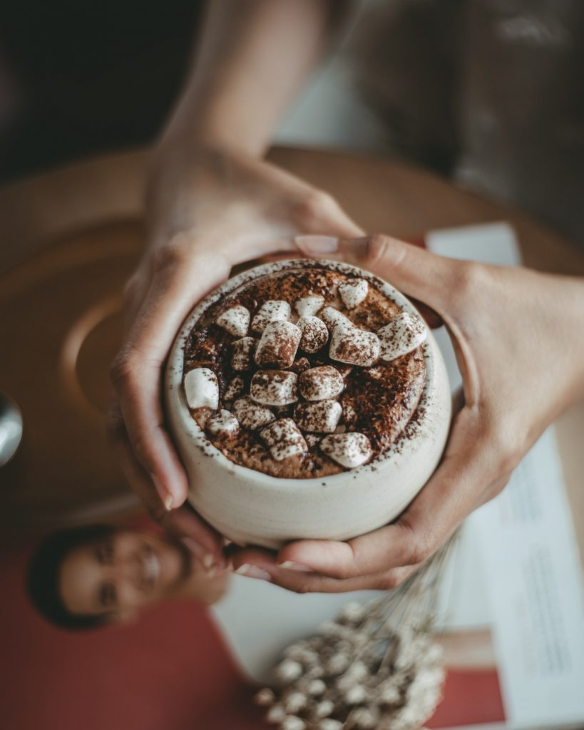 imbolc recipe #7 hot chocolate being held in hands with marshmellows on top