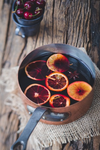 mulled wine in pot with orange slices in it and a cup of cherries behind it