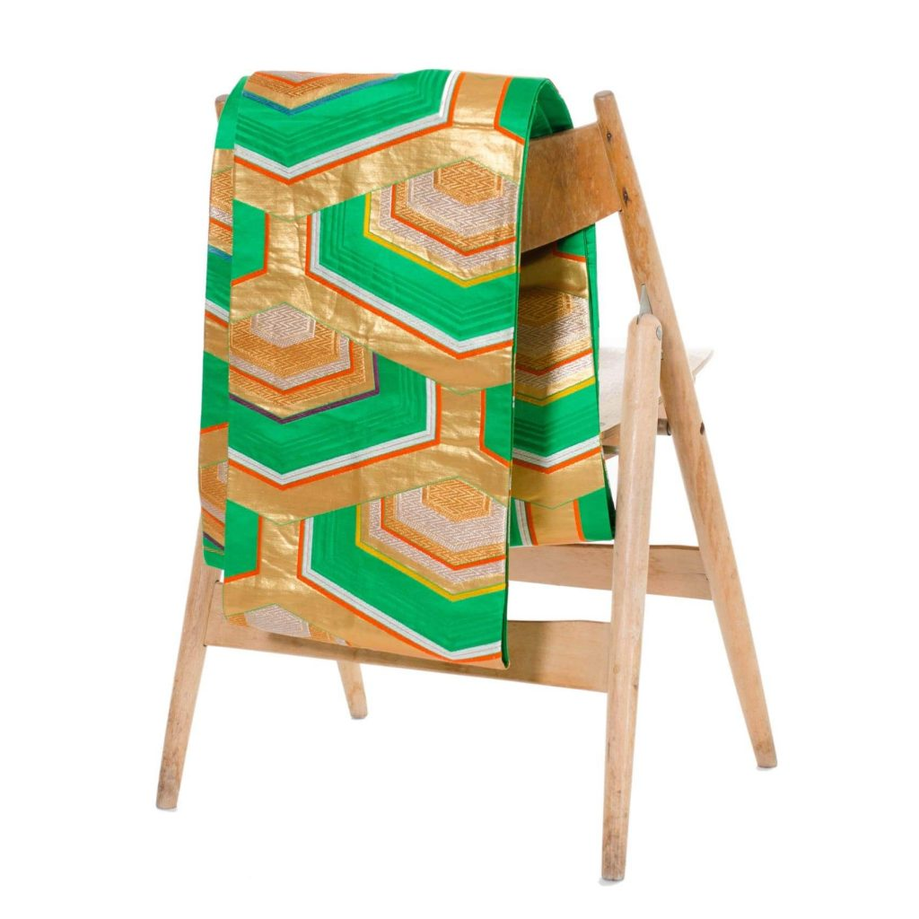 green obi belt with gold accents on the back of a chair