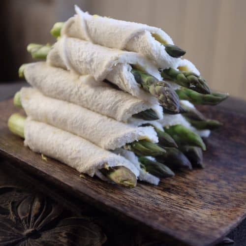pile of asparagus rolls on a wooden board