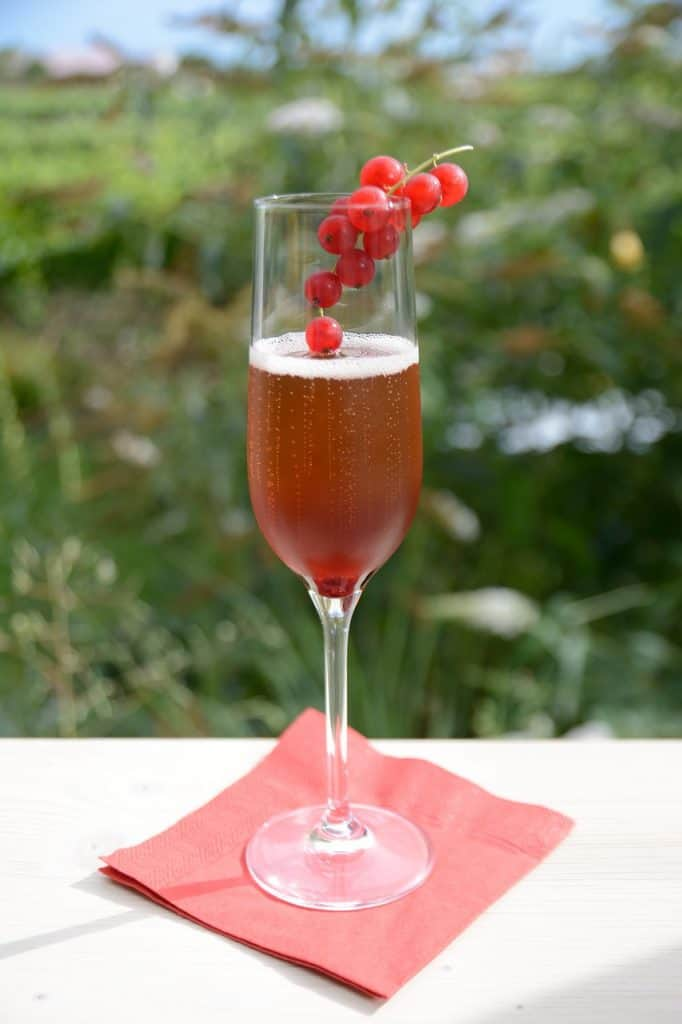kir royal with red currents on rim of glass