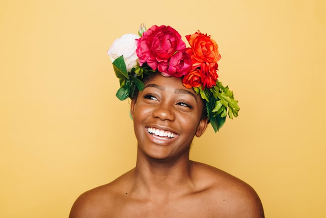 Image of a confident smiling black woman wearing a flower crown on a yellow background
