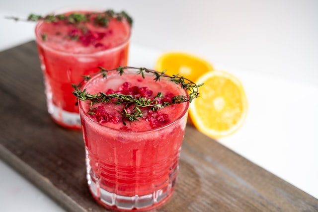 pink cocktail with thyme on top