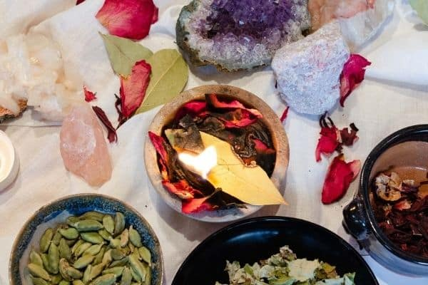 bay leaf with love sigil burning in a fire proof bowl surrounded by love charm ingredients and crystals