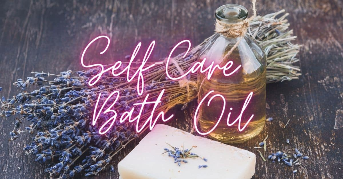 self-care bath oil in neon text written over oil, lavender and soap on a wooden bench