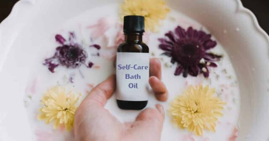 self-care bath oil being held in hands in a milky bowl with flowers around it