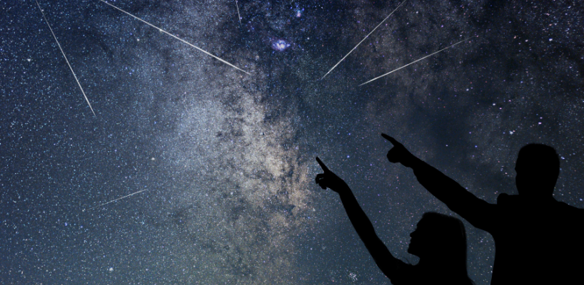 People pointing at a meteor shower